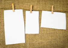 Three blank papers hung from a rustic vintage hanger Stock Photography