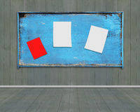 Three blank papers posted on old blue weathered noticeboard Royalty Free Stock Image