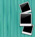 Three blank photo frames on wooden background Royalty Free Stock Photo
