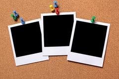 Three blank polaroid frame photo print cork background. Three blank photo prints pinned to a cork notice board. Pathe provided stock image