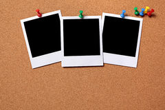 Three blank polaroid frame photo print pushpin cork background. Three blank polaroid photo prints pinned to a cork notice board.  Space for copy.  Paths Stock Photos