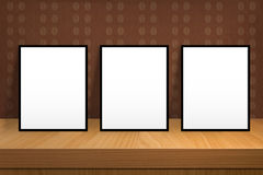 Three blank poster stand on a wooden table over vintage wallpape Royalty Free Stock Photo