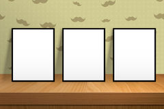 Three blank poster stand on a wooden table over vintage wallpape Royalty Free Stock Photos