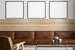 Three blank posters above brown sofa. Three blank posters on light wall above vintage brown leather sofa woth wooden framework in loft style room. 3D rendering Royalty Free Stock Photography