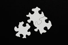 Three blank puzzle pieces on black background one unlinked Stock Photos