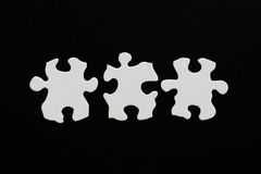 Three blank puzzle pieces inline unlinked on black background Stock Photos