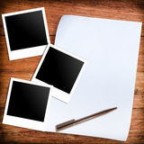 Three blank retro polaroid photo frames and white paper and pen. Over wooden background Royalty Free Stock Images