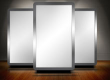 Three blank screens standing on wooden floor Royalty Free Stock Photos