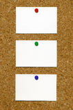 Three blank white business cards on a noticeboard. Stock Photos
