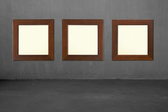 Three blank wooden frames on concrete wall Royalty Free Stock Photos