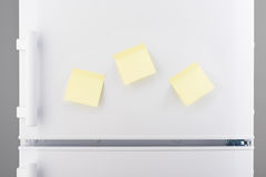 Three blank yellow sticky paper notes on white refrigerator Stock Images