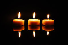 Three blazing wax candles. Standing in a line on a reflective plane Stock Photography
