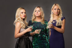 Three blonde girls wearing evening dresses driknking martini Stock Photography