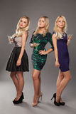 Three blonde girls wearing evening dresses driknking martini Stock Photos