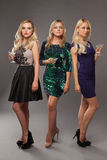 Three blonde girls wearing evening dresses driknking martini Royalty Free Stock Images