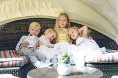 Three blonde seasters and one brother sitting on rattan sofa. Sunny day. children`s party at a restaurant on the street Stock Photos