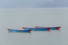 Three blue boats on Phewa Lake in Pokhara Royalty Free Stock Photography