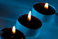 Three blue candles are glowing in the darkness.  Stock Photography