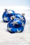 Three blue christmas balls in snow. Three blue christmas balls in the snow with silver star motives Royalty Free Stock Photo