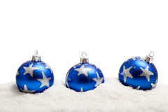 Three blue christmas balls in the snow - isolated. Three blue christmas balls with silver star motives in the snow - isolated Royalty Free Stock Images