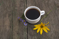 Three blue flowers, one yellow and a cup of coffee on a wooden t Royalty Free Stock Image