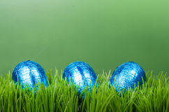 Three blue foil Easter eggs on grass Royalty Free Stock Photos
