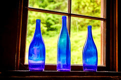 Three Blue Glass Bottles. A still life image of three old cobalt blue glass bottles that are illuminated through a window royalty free stock photography