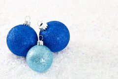 Three Blue Glittery Ornaments on Snowy Background Royalty Free Stock Photos