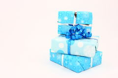 Three Blue Holiday Gifts. Three holiday gifts wrapped in blue snowflake printed paper and photographed on a white background Royalty Free Stock Image