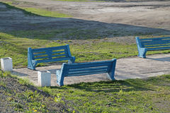 Three blue painted benches standing next to pathway Stock Photos