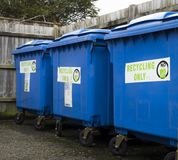 Three blue recycling bins standing in a line. Three large blue industrial size recycling bins standing in a line in perspective Stock Photography