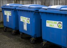 Three blue recycling wheelie bins. Three large blue industrial size recycling wheelie bins standing in line in perspective royalty free stock image