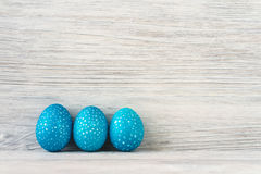 Three blue speckled Easter eggs on a white wooden background Royalty Free Stock Image