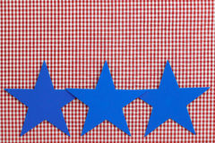 Three blue stars border red checkered (gingham) background. Three blue stars border plaid fabric Stock Photo