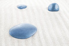 Three blue stones on white sand Stock Photos