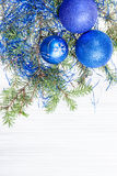 Three blue and violet Xmas balls and twig on paper Royalty Free Stock Photos