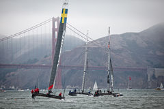 Three boats competing in the Louis Vuitton Cup race in the Americas Cup Series sail in front of the Golden Gate Bridge Royalty Free Stock Photo