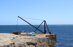 Three Boats and Crane Sitting By The Sea Royalty Free Stock Image