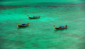 Three boats float in the clear emerald green sea, overlooking the underwater coral reef. Waiting for tourists on Koh Lipe, Satun,. Thailand stock photos