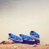 Three boats on the lake with retro filter Royalty Free Stock Photos