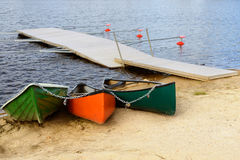 Three boats on shore of blue lake Royalty Free Stock Image