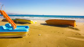 Three boats and a Water slide on the beach on this winter day, waiting for the summer tourism to arrive so to be in the blue sea i stock photos