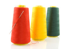 Three bobbins with threads and needle Royalty Free Stock Photo