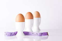 Three boiled eggs with measuring tape royalty free stock image