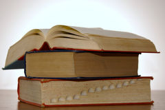 Three books. Stack of three old books, one with pages open, lit from behind Royalty Free Stock Images