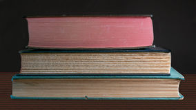 Three books on black. Closeup on the fore edge of three old books stacked on top of each other, on wooden table, against dark background - vintage learning Royalty Free Stock Images