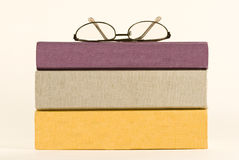 Three Books With Blank Spines. A stack of three books with blank spines and a pair of glasses on top Royalty Free Stock Photo
