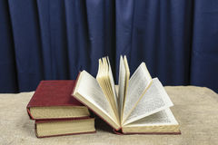 Three books on a blue background. On the gray table Royalty Free Stock Images