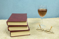 Three books, a glass of wine and glasses. On a blue background Stock Images