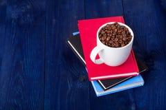 Three books and mug full of coffee beans Royalty Free Stock Photo